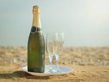 Une bouteille de vin mousseux avec des verres d'un plat blanc Image libre de droits