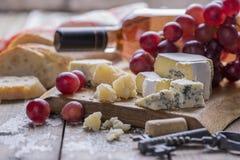 Une bouteille de vin rosé, raisins, fromage, liège, tire-bouchon, le pain blanc a servi avec une serviette de textile sur un fond photo stock