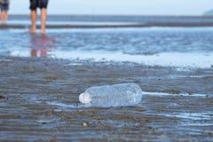 Une bouteille en plastique d'eau potable salissant sur la plage avec des vagues fond et les gens de mer marchant au sol images stock