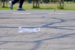 Une bouteille en plastique d'eau potable salissant sur le rez-de-chaussée de route au parc vert avec un homme courant sur la voie images stock