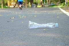 Une bouteille en plastique d'eau potable salissant sur le rez-de-chauss?e de rue au parc vert photographie stock libre de droits
