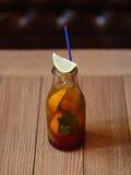 Une bouteille en verre avec une boisson fraîche régénératrice, une tranche de chaux parfumée sur un fond en bois brouillé Photo stock