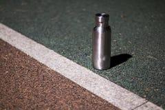 Une bouteille isolée d'acier inoxydable à la voie pendant la nuit images libres de droits