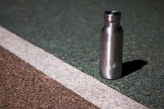 Une bouteille isolée d'acier inoxydable à la voie pendant la nuit photo libre de droits