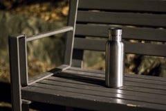 Une bouteille isolée d'acier inoxydable sur le banc dans la forêt de nuit photo libre de droits