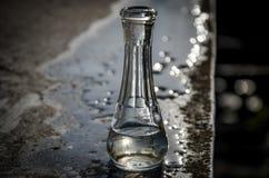 Une bouteille sur une table humide Photos libres de droits