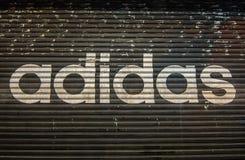 Une boutique fermée de ` d'Adidas la nuit en dehors du magasin Photo libre de droits