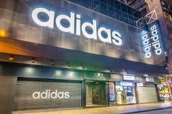 Une boutique fermée de ` d'Adidas la nuit en dehors du magasin Image libre de droits