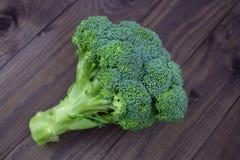 Une branche de brocoli vert sur une table en bois foncée Brocoli vert frais appétissant, fleurons verts de feuilles de brins vega image stock