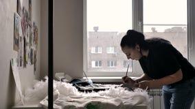 Une brune dans un T-shirt noir et des jeans dessine clips vidéos