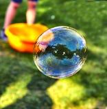Une bulle de savon vole dans la perspective de l'herbe verte photo stock