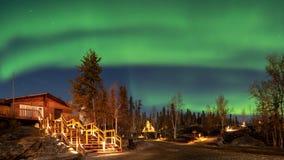 Une cabine de rondin dans la forêt de pin sous l'aurora borealis à Yellowknife photographie stock libre de droits