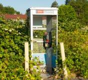 Une cabine téléphonique couverte de feuillage à une station service dans le Canada Photographie stock libre de droits