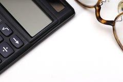 une calculatrice et une paire de verres Photos stock