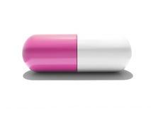 Une capsule rose et blanche d'isolement Photo stock