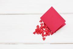Une carte rouge se trouvant sur plusieurs petits coeurs sur le fond en bois blanc Images stock