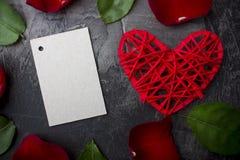 Une carte vierge pour une signature parmi les feuilles d'une rose et d'un coeur rouge sur un fond foncé Photos stock