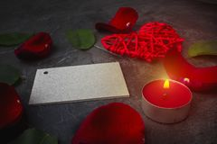 Une carte vierge pour une signature parmi les feuilles d'une rose et d'un coeur rouge sur un fond foncé Jour ou mariage du ` s de Photo stock