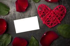 Une carte vierge pour une signature parmi les fleurs d'une rose et d'un coeur rouge sur un fond foncé Photographie stock libre de droits