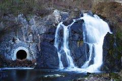 Une cascade avec une entrée mystérieuse de caverne image stock