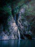 Une cascade grande tombe d'une falaise dans un lac clair la nuit, allumé par la lumière de la lune photo stock
