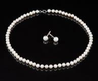 Une chaîne de caractères des perles et des boucles d'oreille Photos stock