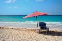 Une chaise avec le parapluie en plage tropicale Photographie stock