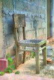 Une chaise cassée se tient devant une maison photo libre de droits