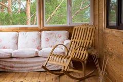 Une chaise de basculage en bois et un sofa sur le porche ou terrasse avec vue sur la forêt photo stock