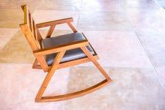 Une chaise de basculage en bois moderne sur le plancher coloré de ciment photos stock