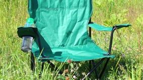 Une chaise de pique-nique se tient sur un pré lumière-inondé Les herbes et les fleurs balancent du vent d'été clips vidéos