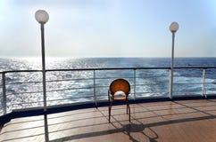 Une chaise sur la plate-forme d'un bateau de croisière Photographie stock libre de droits