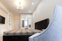 Une chambre à coucher en couleurs les couleurs claires avec un lit foncé et une chaise molle avec des rivets dans le premier plan Images stock