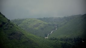 Une Chambre au sous-sol des chutes de l'eau parmi des collines et greenary photographie stock