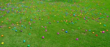Une chasse à oeuf de pâques avec les oeufs en plastique sur une pelouse verte image libre de droits