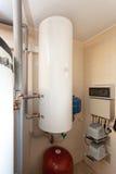 Une chaufferie domestique de ménage avec une nouvelle chaudière moderne de combustible solide, un circuit et des tuyaux de refroi Images libres de droits
