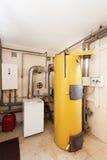 Une chaufferie domestique de ménage avec une nouvelle chaudière moderne de combustible solide, un circuit et des tuyaux de refroi Photo libre de droits