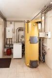 Une chaufferie domestique de ménage avec une nouvelle chaudière moderne de combustible solide, un circuit et des tuyaux de refroi Photos stock