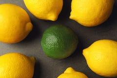 Une chaux parmi des citrons sur le fond gris Photos stock