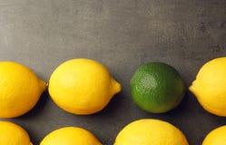 Une chaux parmi des citrons sur le fond gris Photo libre de droits