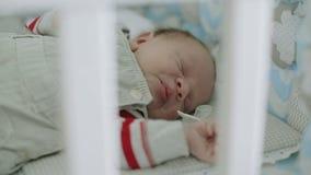 Une chute infantile de garçon endormie dans son berceau banque de vidéos