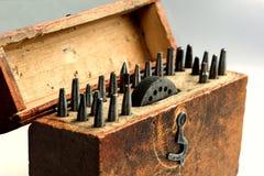 Une circulaire de cru autour des poinçons faisants le coin réglés avec une enclume avec des ouvertures dans une boîte en bois photo stock