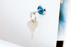 Une clé dans un trou de la serrure Photo stock