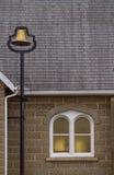 Une cloche d'or par une fenêtre d'église Photos stock