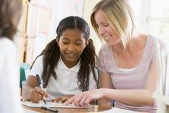 Une écolière s'asseyant avec son professeur dans la classe Photographie stock libre de droits