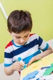 Une colle préscolaire d'utilisation de garçon pour le travail photographie stock libre de droits