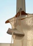 Une composition avec une robe blanche de dentelle, une paire d'espadrilles et un collier de perle accrochant sur un cintre en boi Photographie stock