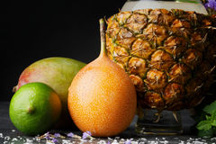 Une composition des fruits d'été Agrumes colorés et une tasse d'ananas Mangue, chaux, et pamplemousse sur un fond noir photographie stock libre de droits