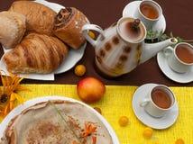 Une composition extérieure avec des tasses de thé, un pot de thé, un plat des crêpes, la pâtisserie, le fruit mûr et le champ fle Photographie stock libre de droits