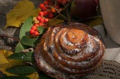 Une composition lumineuse en A avec une tasse de thé noir fort, d'un petit pain doux avec des raisins secs, de baies de cendre, d Photographie stock